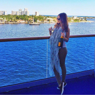 Marianna Hewitt enjoying a bottle of champagne while on her Caribbean cruise while wrapped in a Mangrove scarf.  Channel your inner fashionista, buy this scarf on our E boutique.